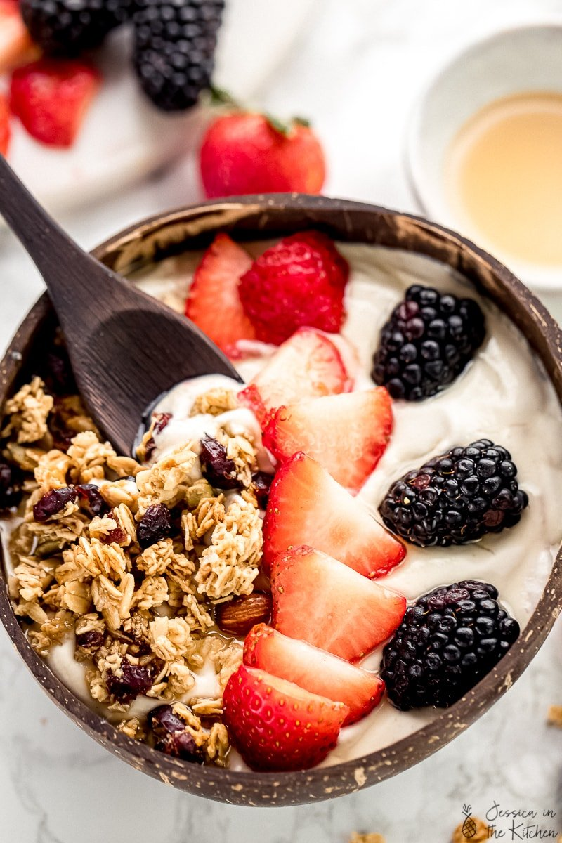 A spoon dipping into a bowl of vegan yogurt, topped with berries and granola.