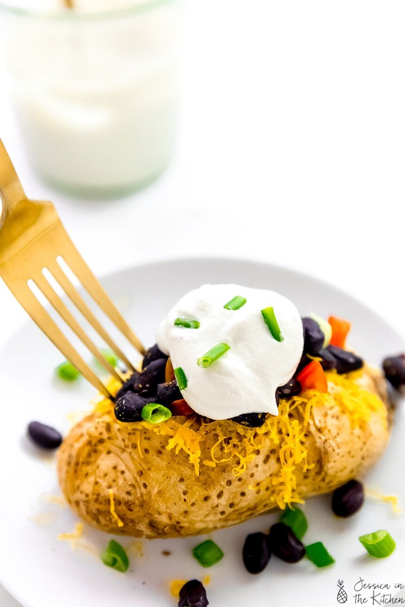 A fork digging into a cheesy baked potato with sour cream on top.
