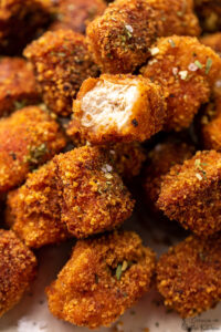 Closeup of vegan tofu nuggets, one with a bite taken out.