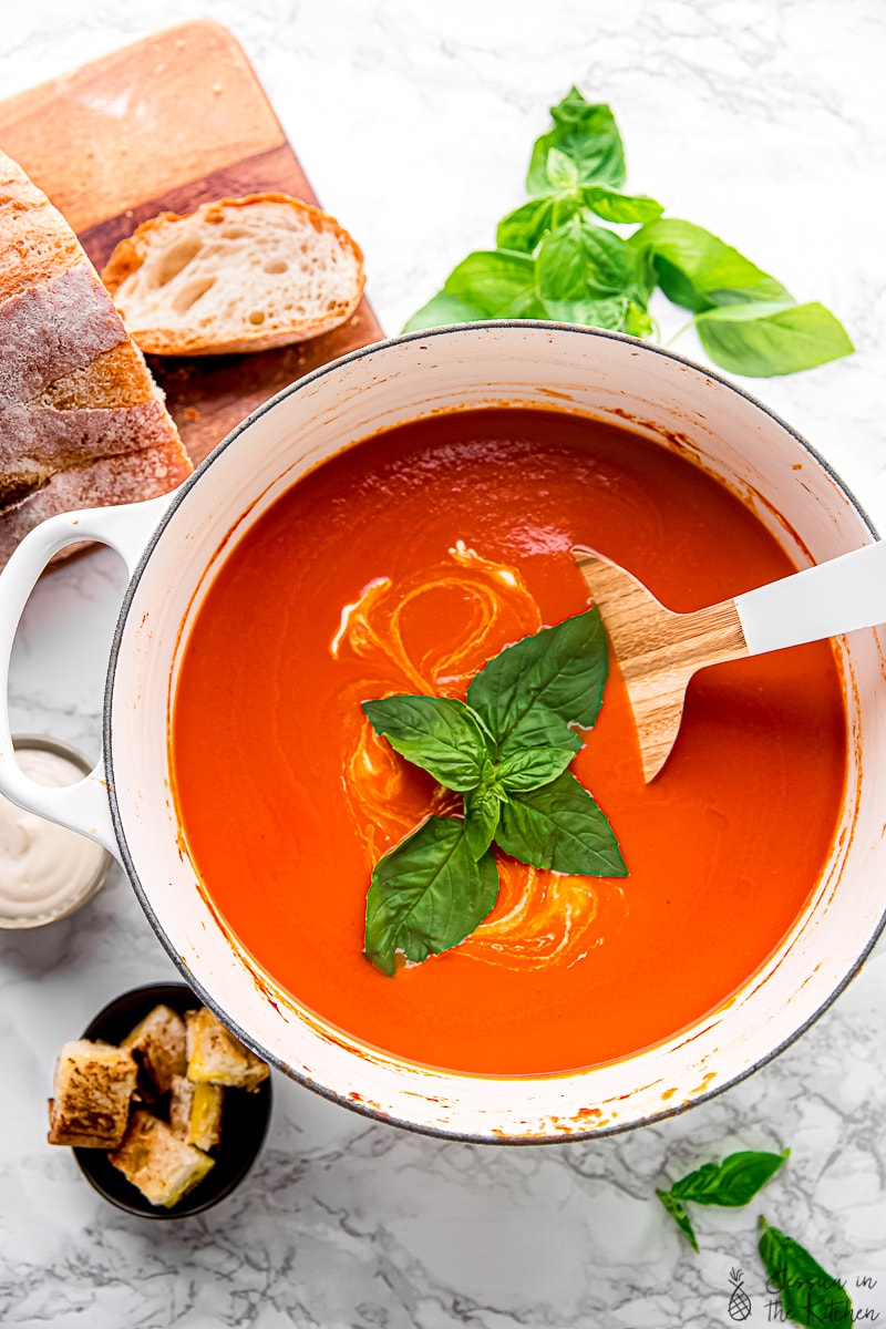 Creamy tomato soup in a pot with croutons on the side.
