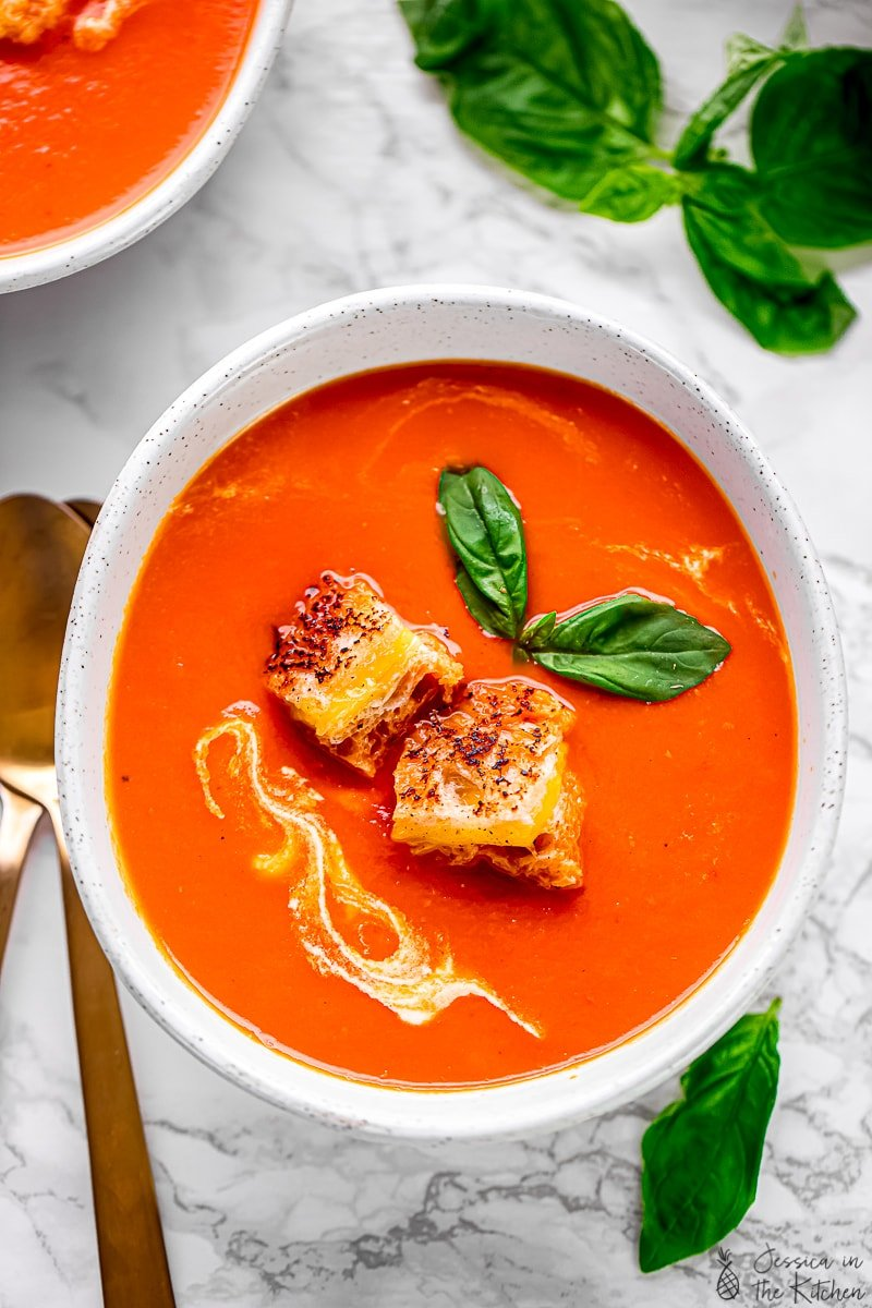 Top down view of creamy tomato soup, topped with cheesy croutons.