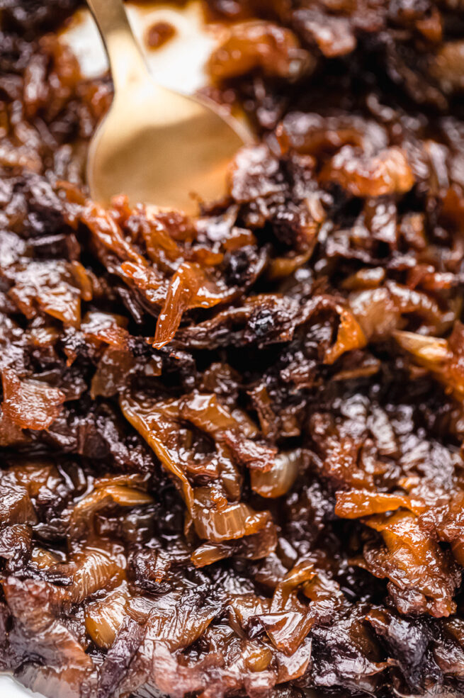 A gold spoon stirring caramelized onions in a skillet.