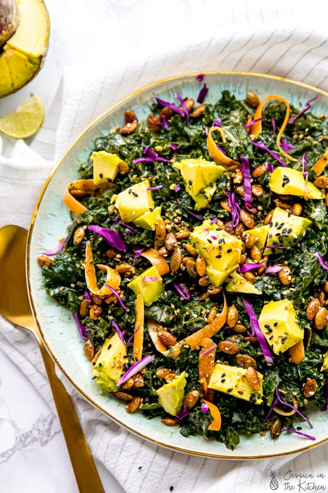 Overhead view of the best kale salad, drizzled with tahini dressing.