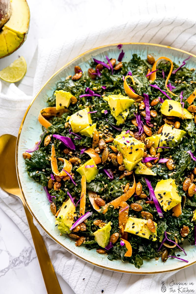 Top down view of the best kale salad in a blue bowl with a gold spoon on the side.