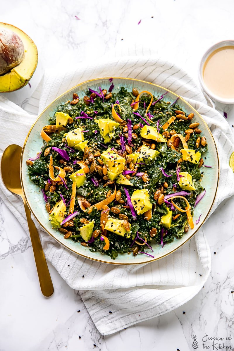 Top down shot of kale salad with a sesame tahini dressing.
