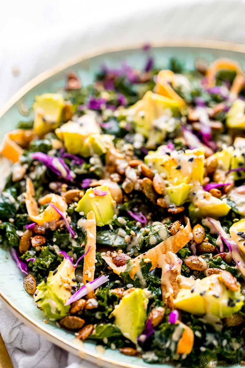 Close up of a kale salad, topped with diced avocado.