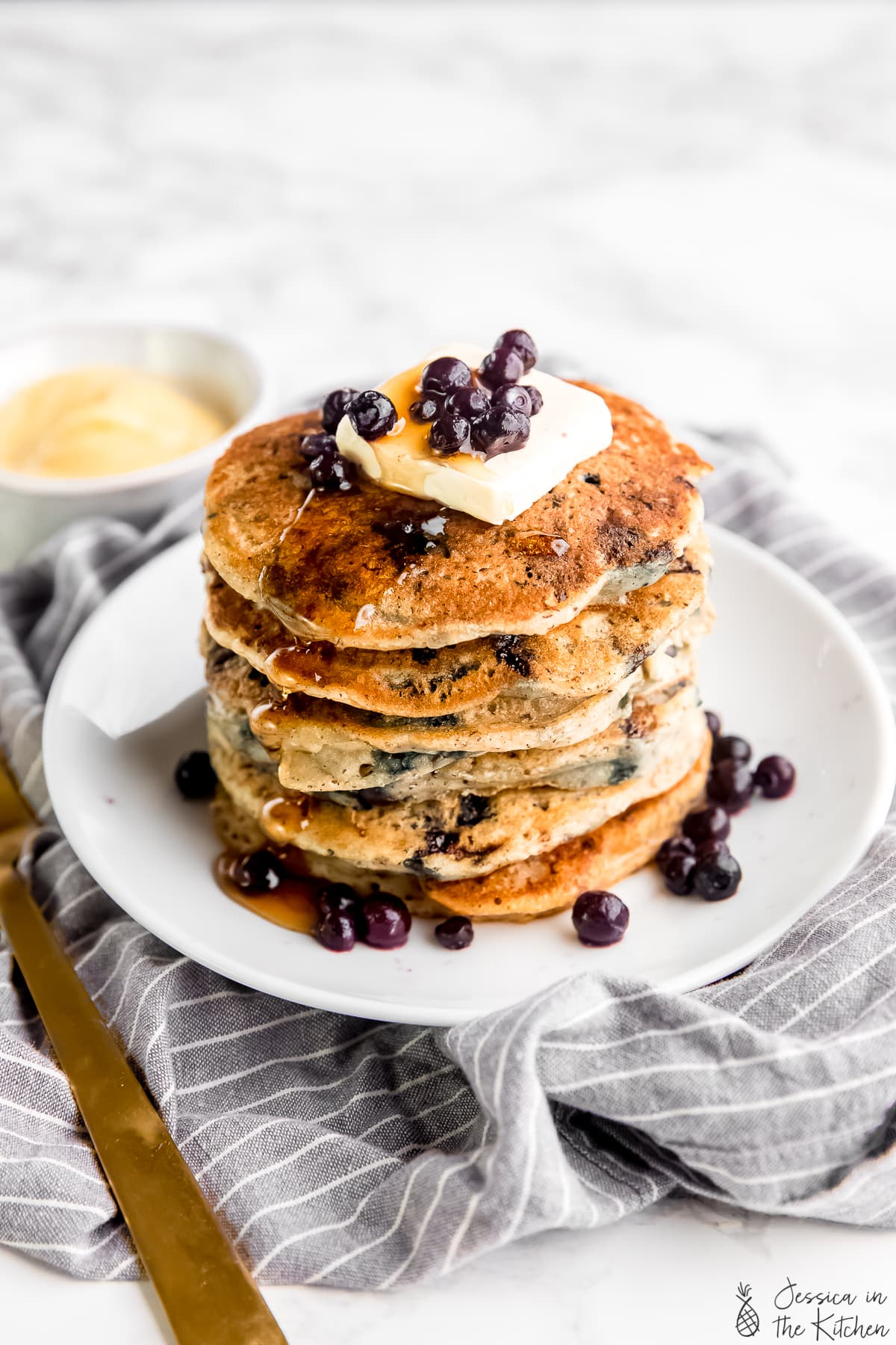 Vegan pancakes stacked on a plate, covered with syrup and blueberries.