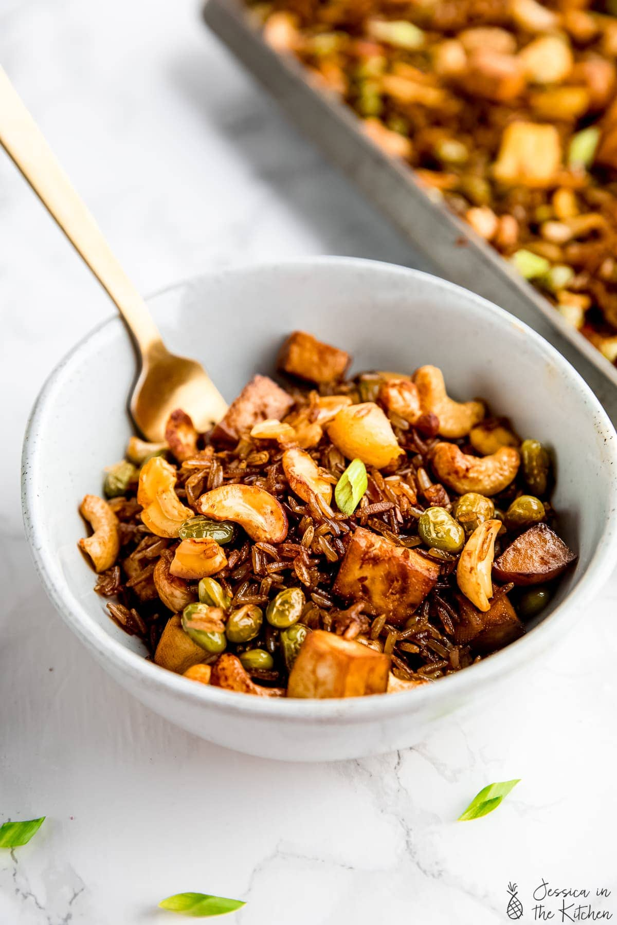 A bowl of vegan fried rice with a fork sticking in.