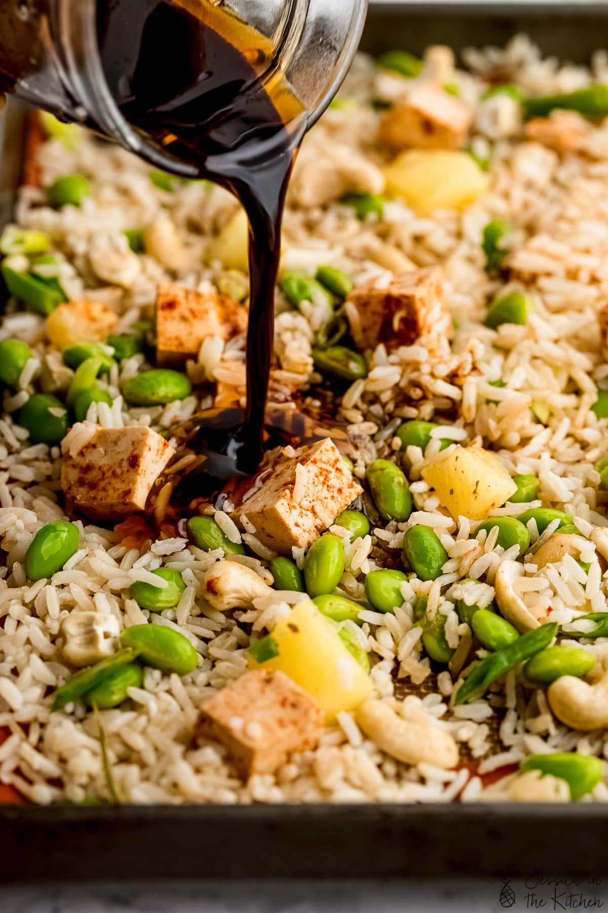 Pouring sauce on vegan fried rice.