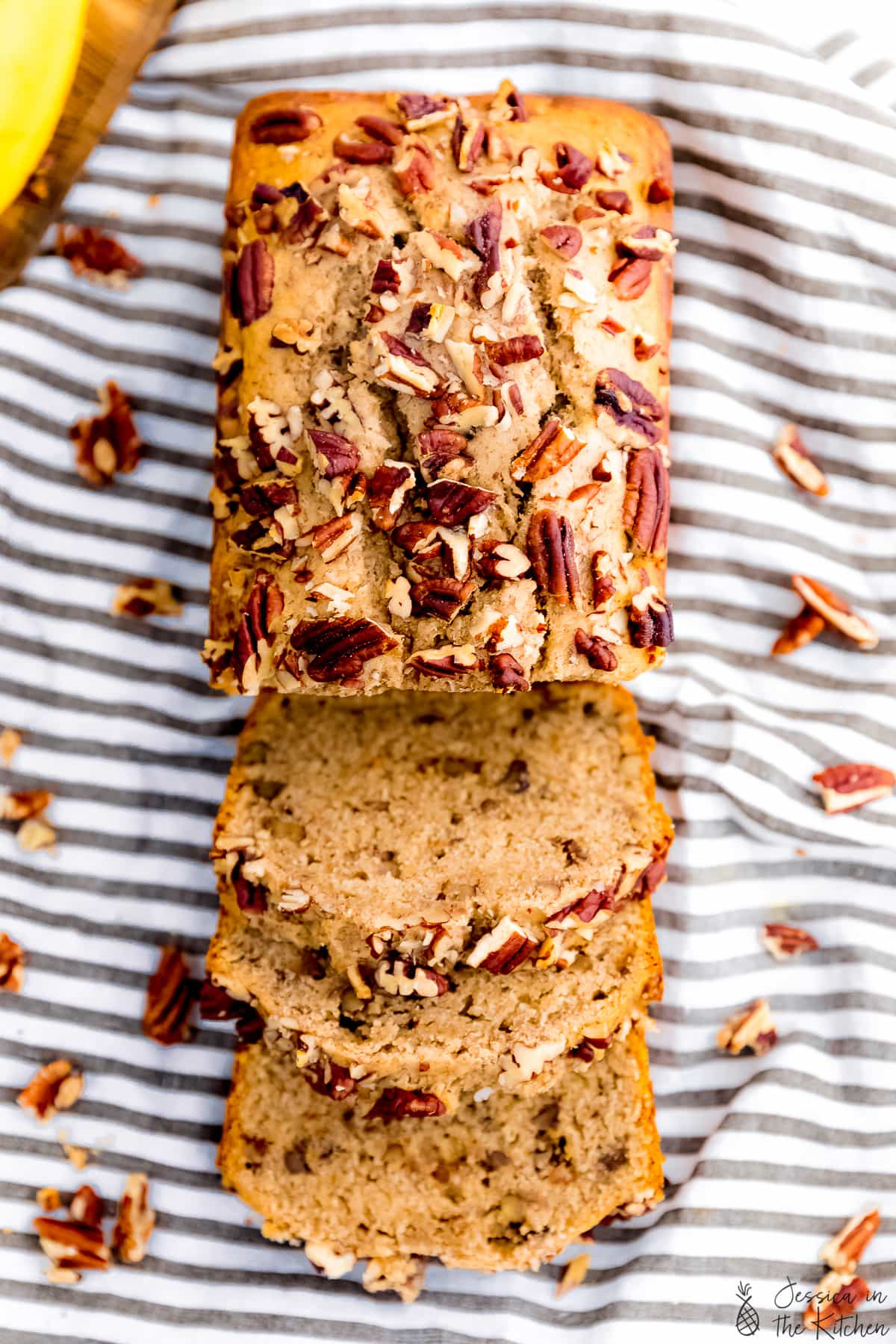 vegan banana bread with half of it sliced into three slices, then the rest whole, birds eye view, surrounded by pecans