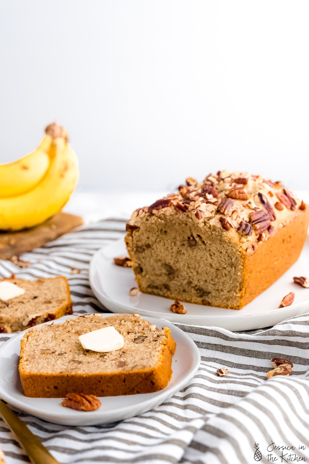 slice of banana bread on a plate with the rest on a platter in the background with a bunch of bananas in the left hand corner