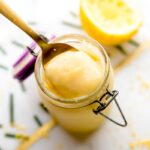 A gold spoon scooping out vegan lemon curd from a little glass jar.