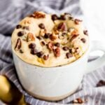 Banana bread mug cake in a mug with a golden spoon in front.