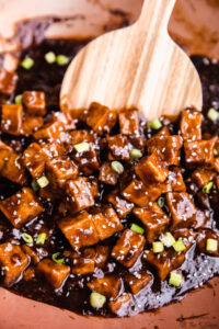 General tso tofu being stirred in a pot.