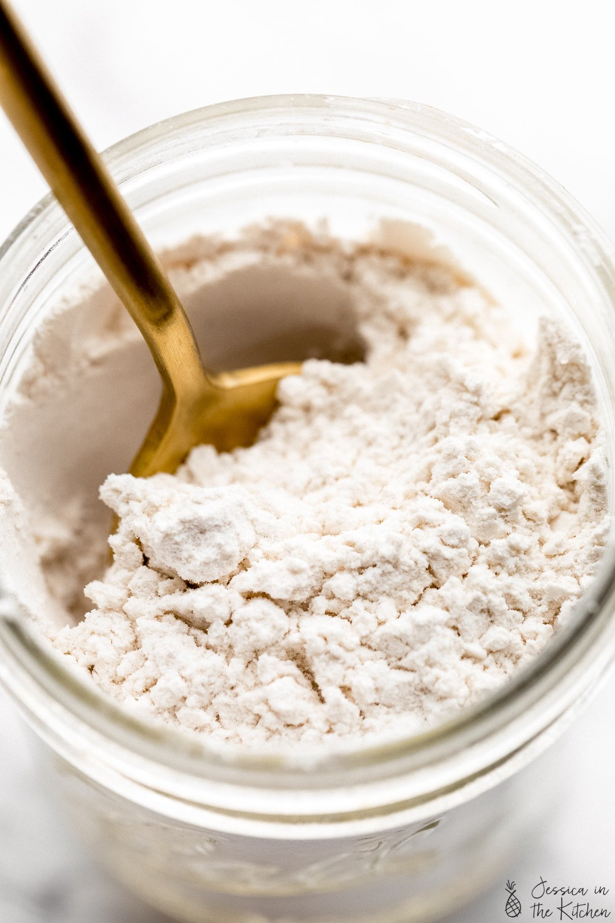 Easy homemade powered sugar in a glass Weck jar with a gold spoon in the powder.