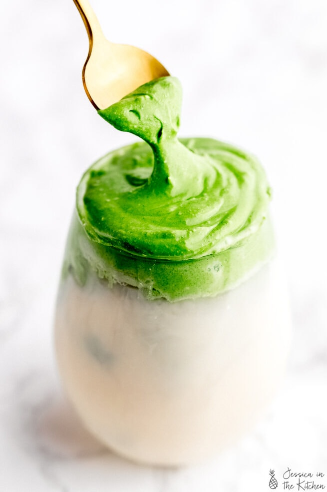 whipped matcha in a glass with milk with a gold spoon pulling the whipped matcha froth