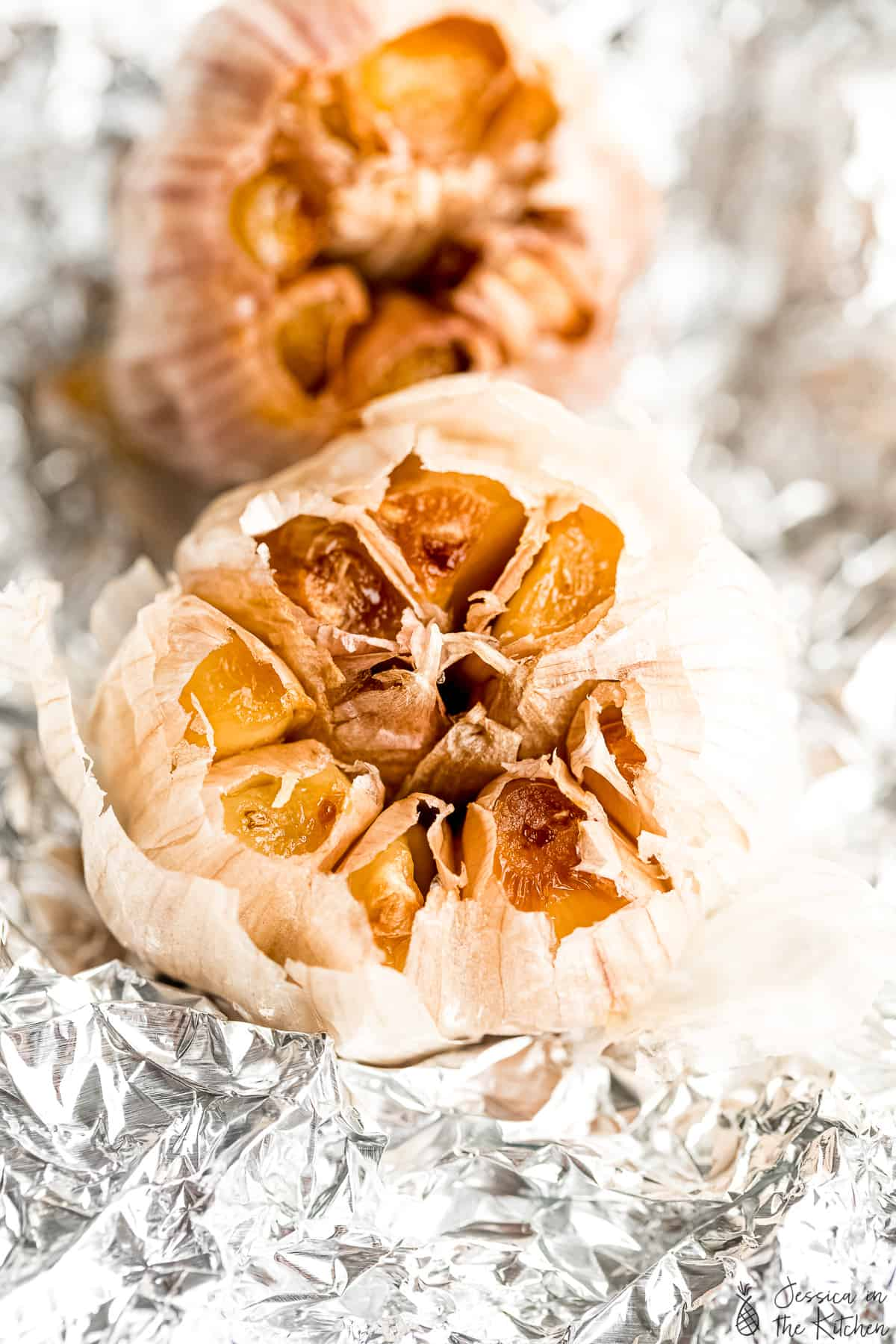 Overhead view of two roasted garlic bulbs on foil.