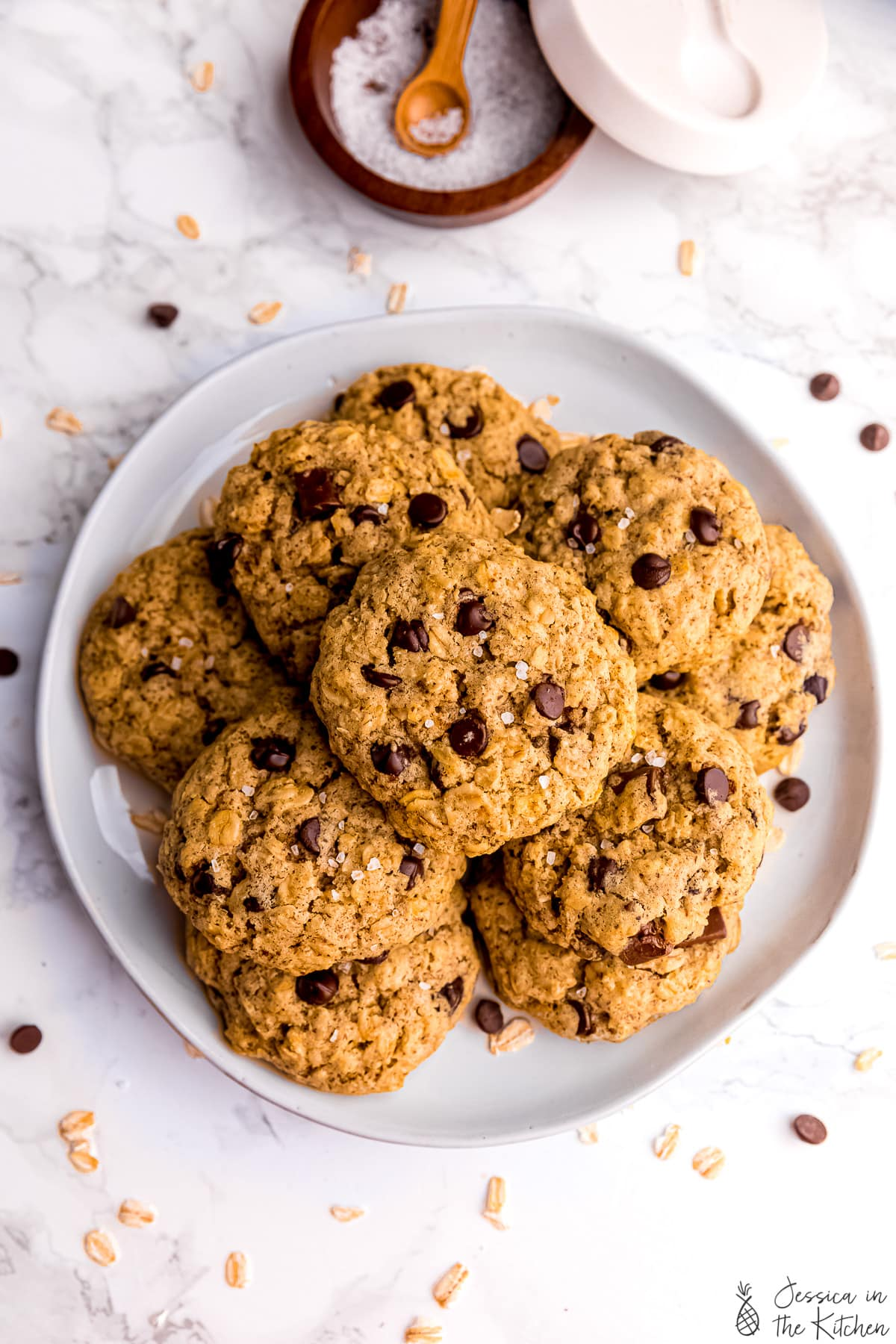 Top down view of oatmeal chocolate chip cookies on a plate with a pot of salt on the side.