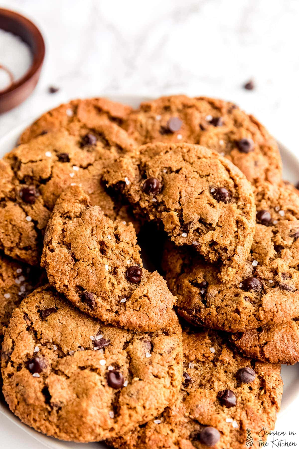 5 ingredient chocolate chip cookies stacked on each other on a plate in front of a jar of salt one of the cookies on top broken in half