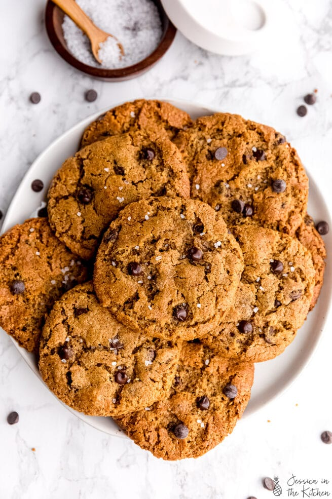 Five ingredient chocolate chip cookies stacked on each other on a plate in front of a jar of salt