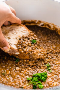 Bread dipped into a pot of lentil stew.