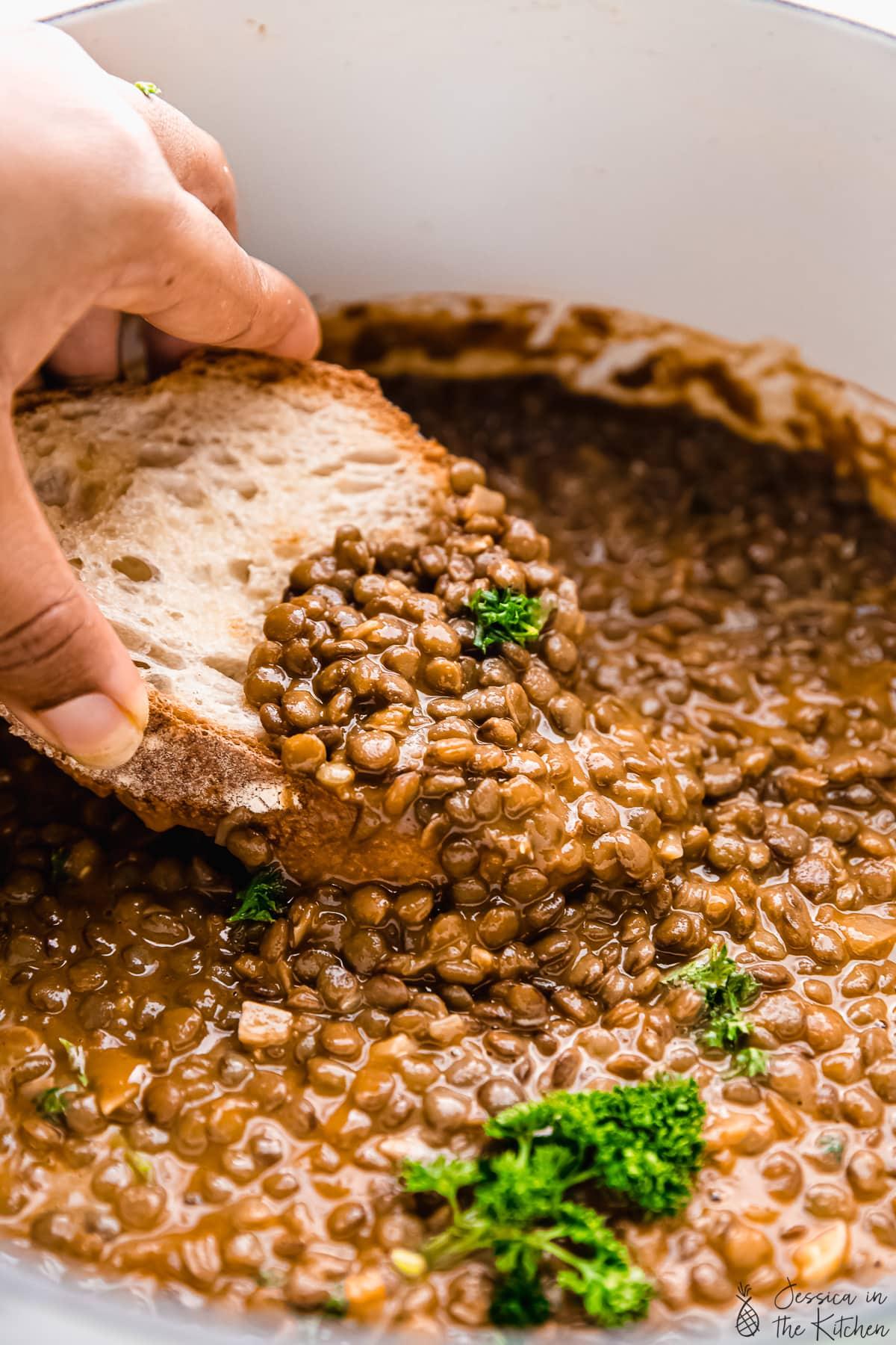 Hand dipping bread into vegan lentil stew.