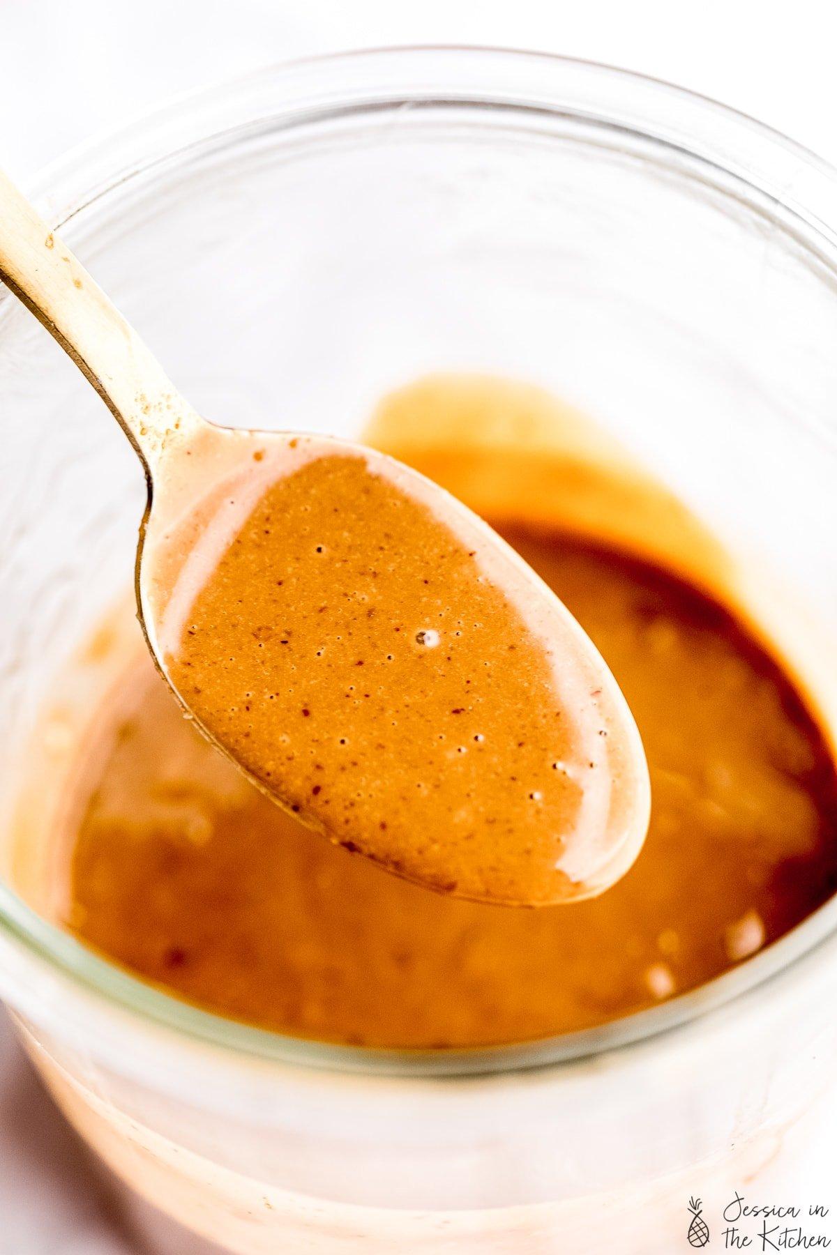 Thai peanut sauce in a gold spoon over a jar