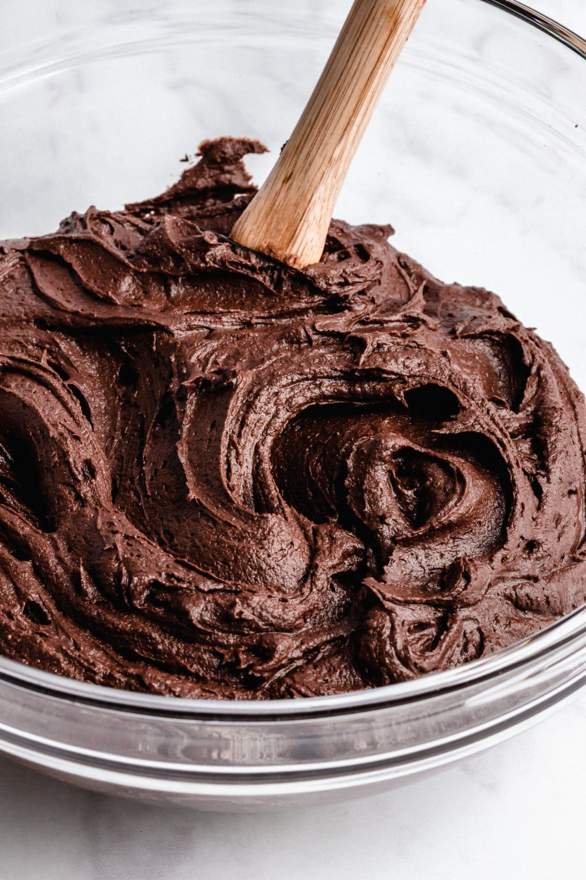 A bowl of vegan chocolate frosting with a spatula in it.