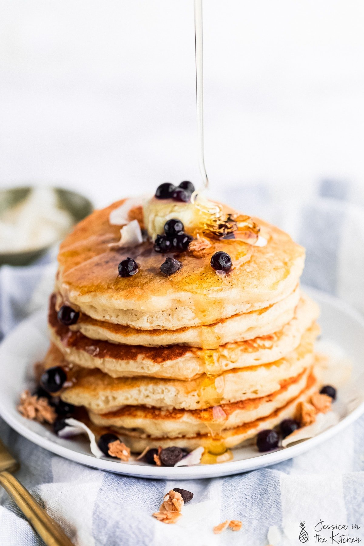 syrup pouring on top of a stack of pancakes