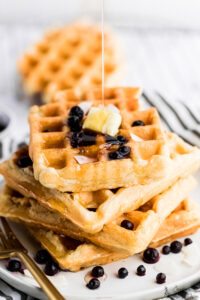 vegan waffles stacked on top of each other with maple syrup drizzle on top