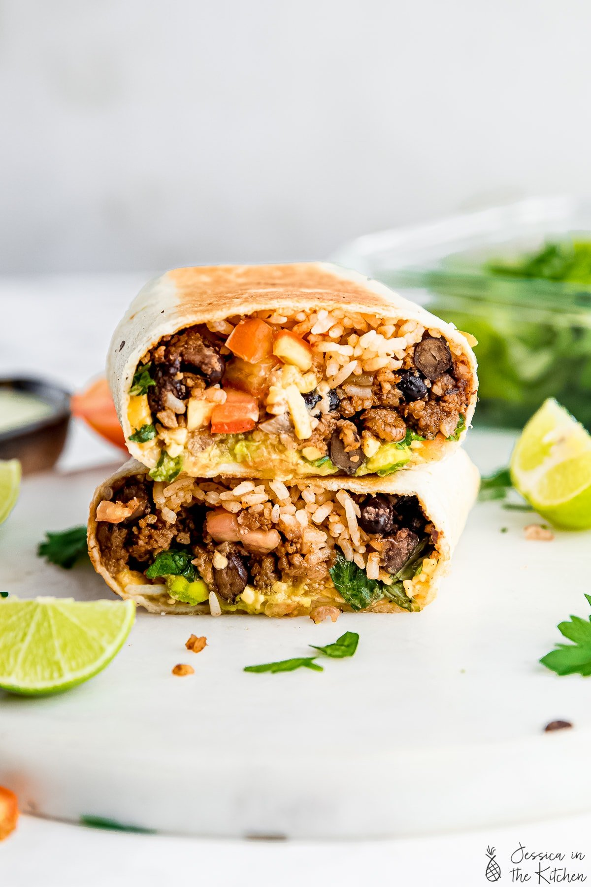 stacked Vegan burrito on a white cutting board surrounded by lime, parsley and ingredients