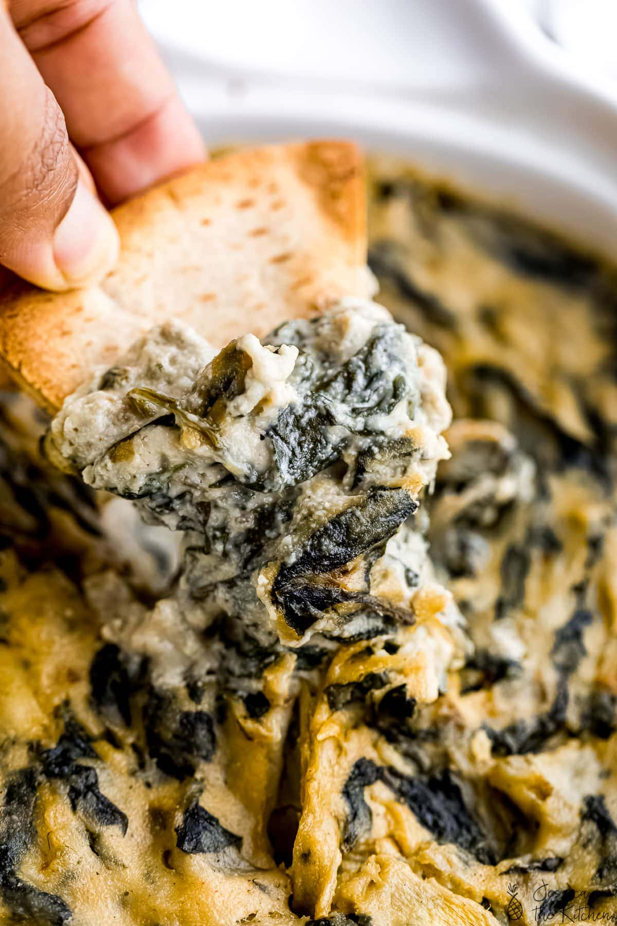 Close up shot of spinach artichoke dip on a pita chip.