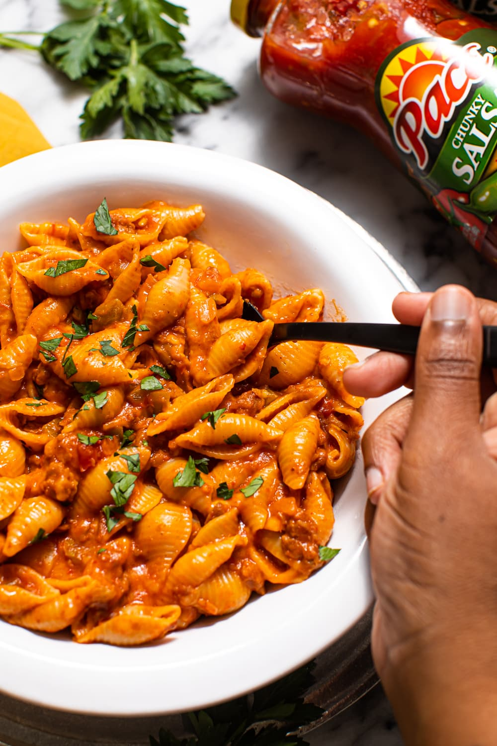 photo of creamy salsa pasta with a fork in the white bowl with a hand holding the fork