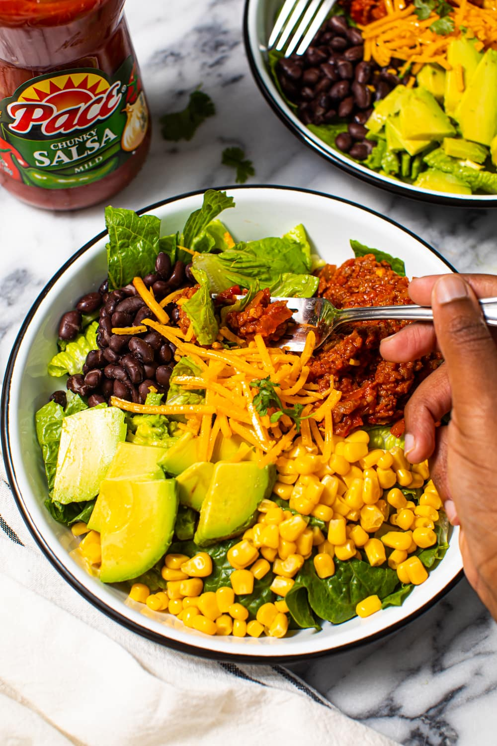 bowl of salad with black beans, sliced avocado, sweet corn, vegan cheese, lettuce, and vegan meat seasoned in salsa and taco seasoning with fork in it from an overhead view, with fork and a hand holding the fork in it