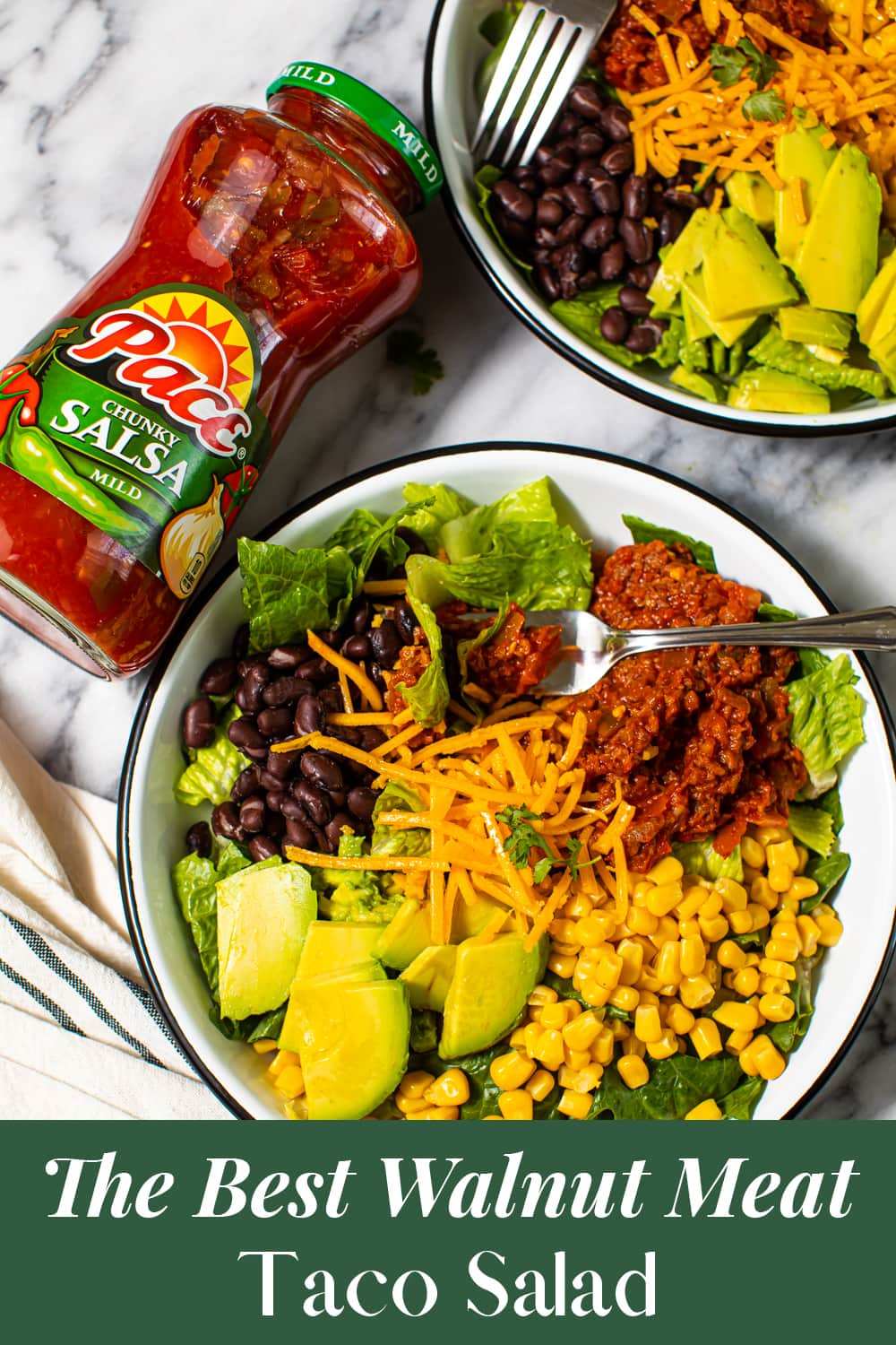 bowl of salad with black beans, sliced avocado, sweet corn, vegan cheese, lettuce, and vegan meat seasoned in salsa and taco seasoning with fork in it from an overhead view, with a jar of salsa to the side, and another bowl of the same salad behind it