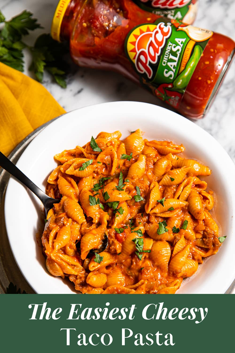 Overhead view of vegan pasta in a bowl next to a jar of salsa.