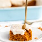 A fork being stuck into a pumpkin cake on a plate with a bite missing in front of a blue container filled with slices of cake.