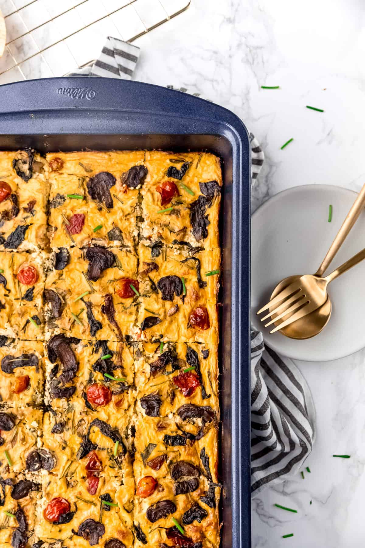 Frittata on a sheet pan sliced with plate with utensils beside it.