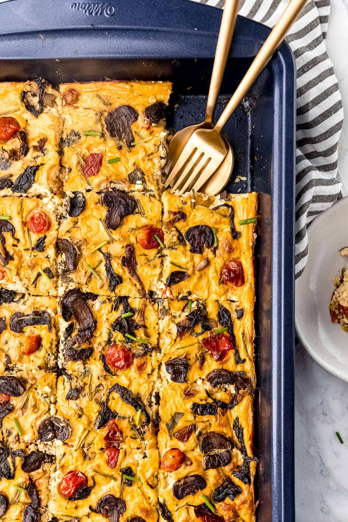 Vegan frittata in a baking sheet with fork and spoon in it.