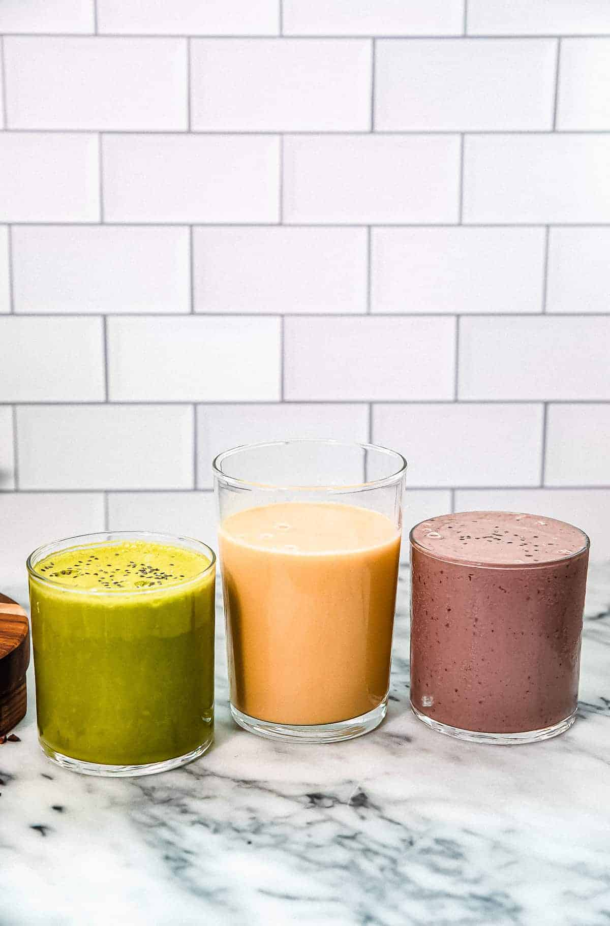 three smoothies green orange and purple on a marble countertop