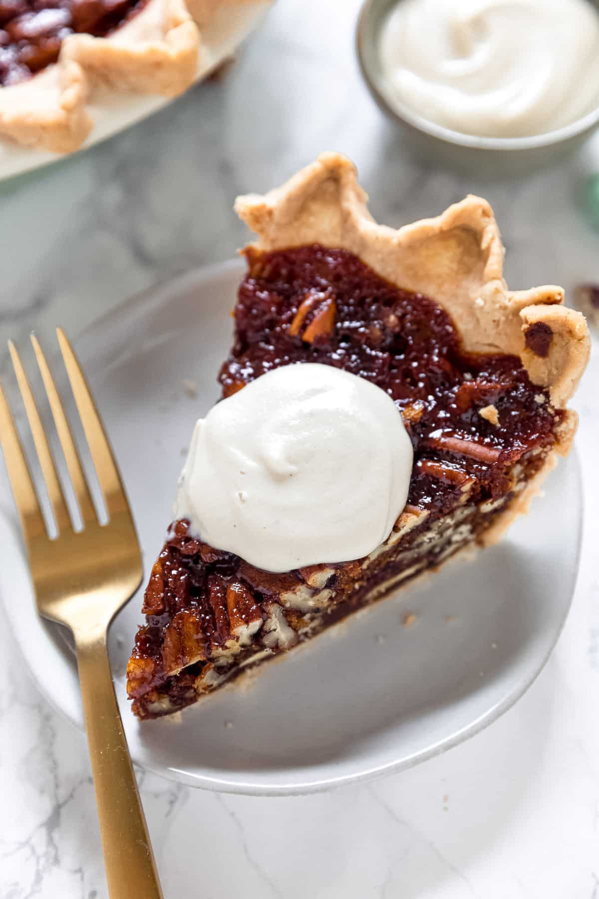 slice of vegan pecan pie on a plate with a dollop of whipped cream on top