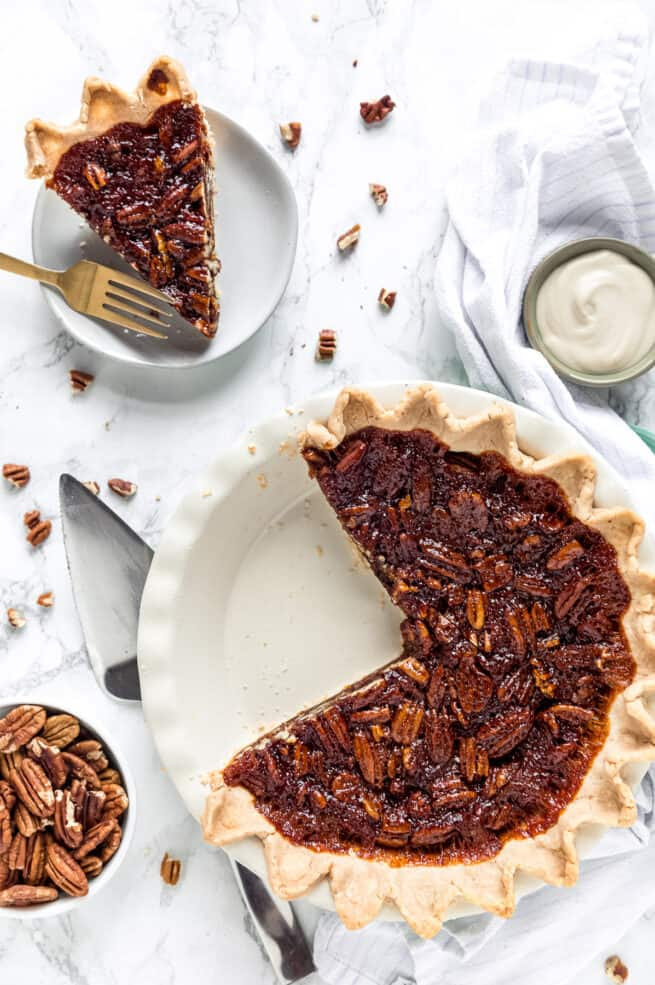 pecan pie with a slice on a plate and the rest of the pie in pie dish