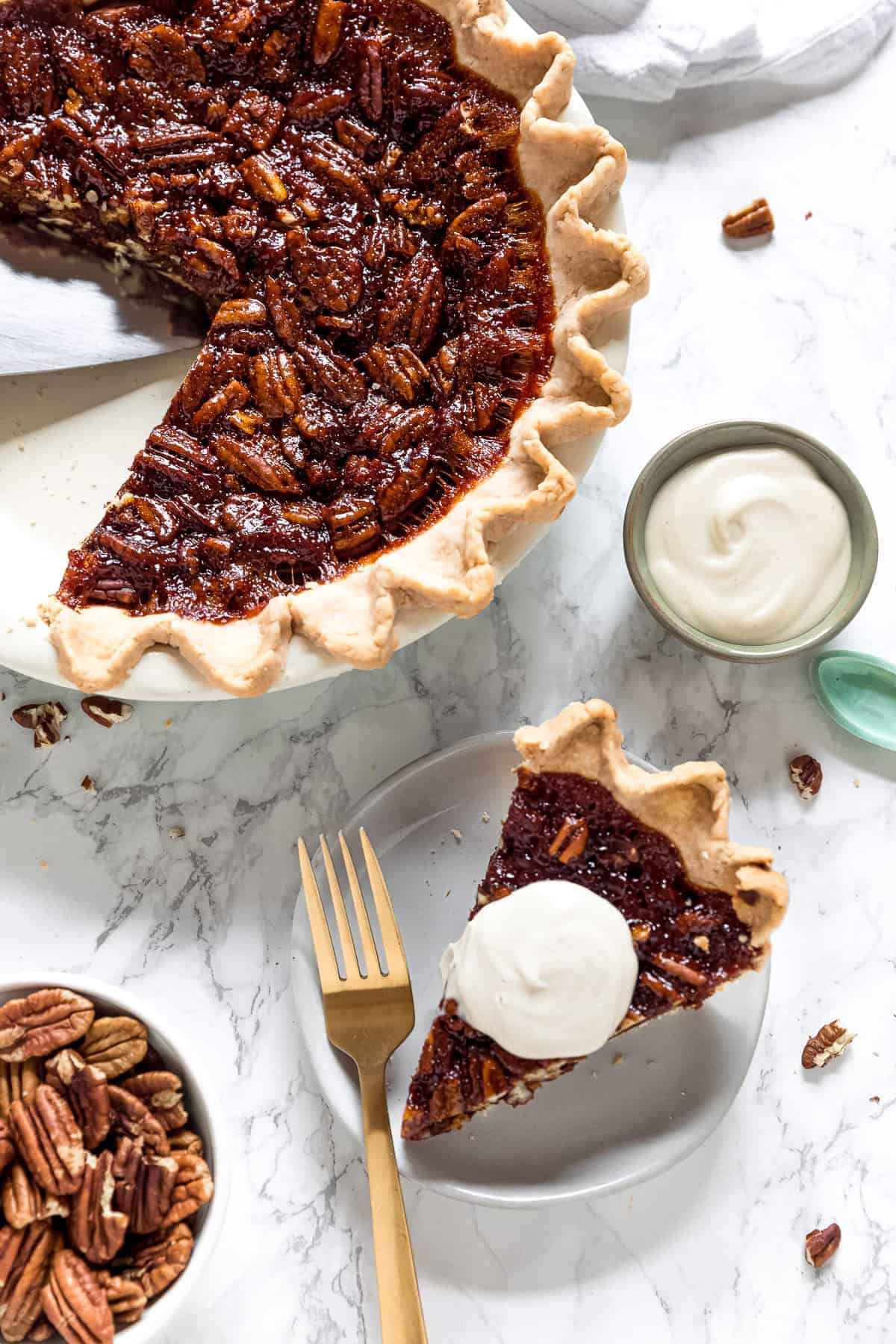 vegan pecan pie with a slice on a plate with cream on top and the rest of the pie in pie dish