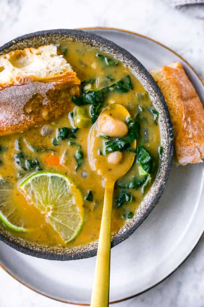 a bowl of white bean soup with a gold spoon inside, bread, lime and kale