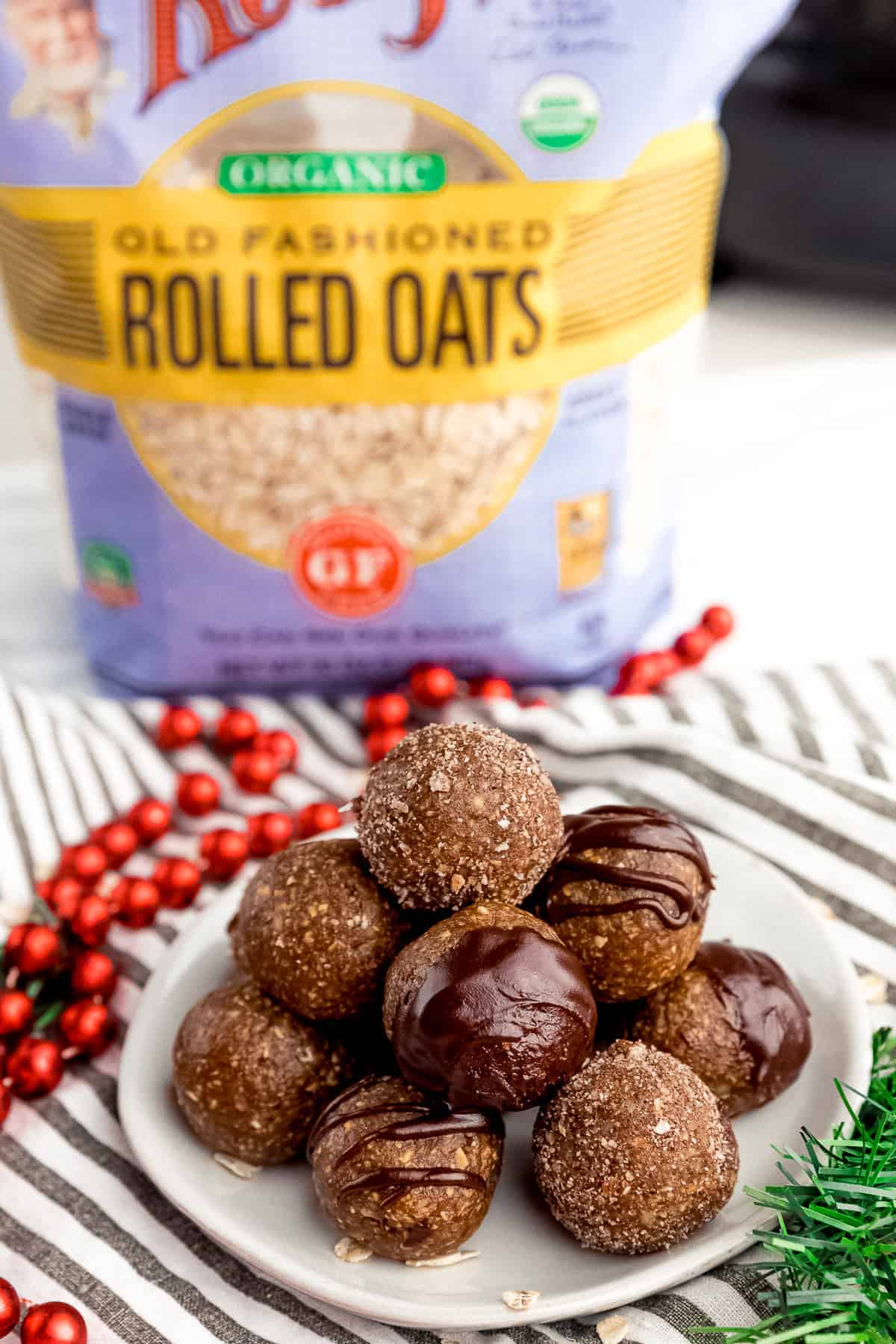 gingerbread energy bites on a plate with a bag of Bob's Red Mill Gluten Free Organic Old Fashioned Oats in the back