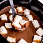 a ladle in a slow cooker filled with hot cocoa and vegan marshmallows with some cocoa and three marshmallows on ladle