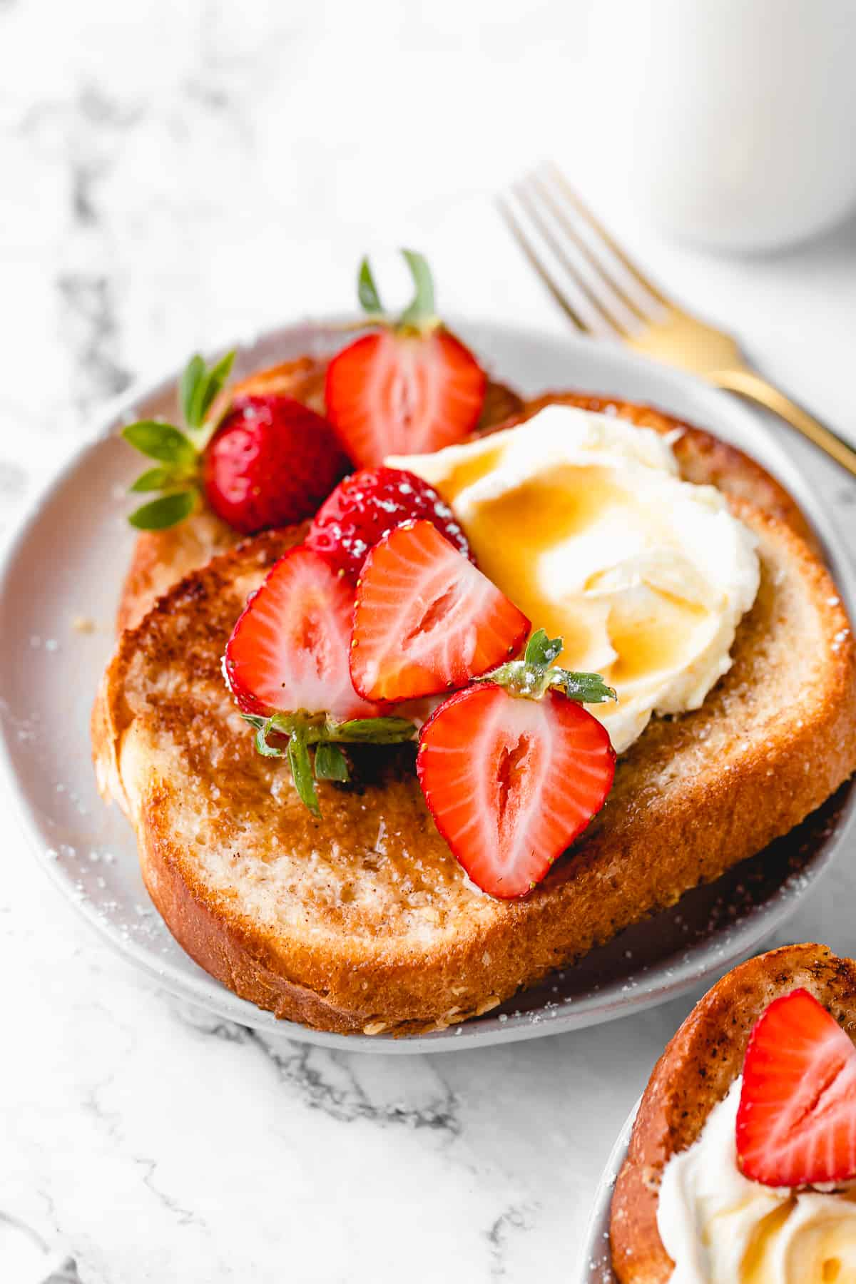 French toast with whipped cream, maple syrup, and strawberries.