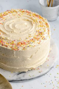 Vegan vanilla cake with buttercream frosting and sprinkles.