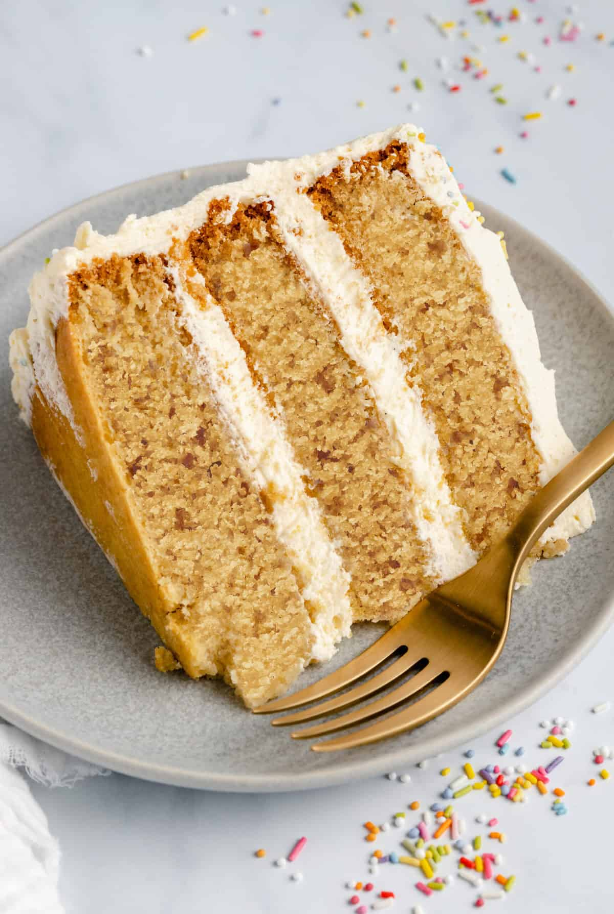 slice of vanilla cake sideways on a plate with gold fork in front of it