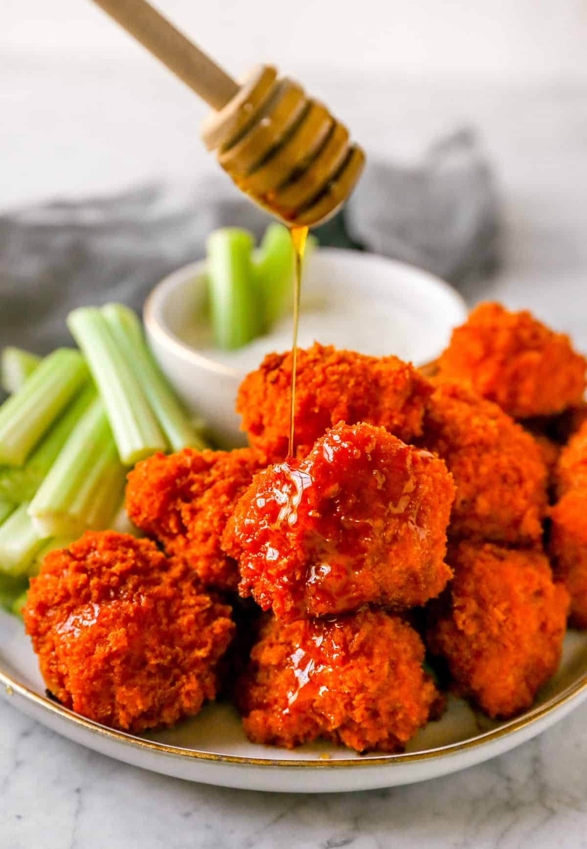 buffalo cauliflower wings on a plate drizzled with maple syrup on a dripper